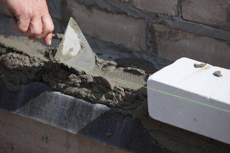 brick building: Builder lays Bricks in cement mortar