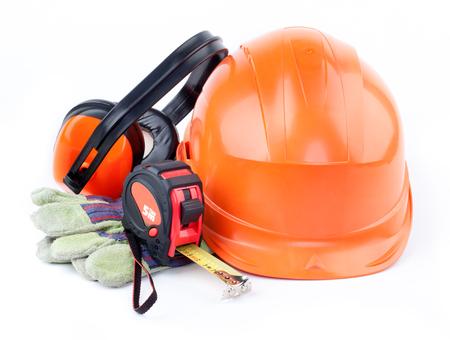 Orange plastic construction Helmet, roulette, gloves, headphones on a white background Stock Photo