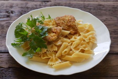 Plate of pasta and meat on a wooden background Standard-Bild