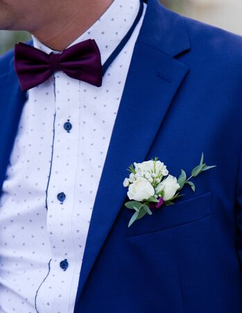 Groom in a blue Suit with a boutonniere close-up