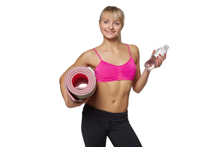 Woman holding yoga mat and water photo