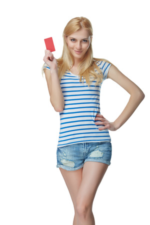 denim shorts: Young slim tanned female in denim shorts, showing blank credit card, isolated on white
