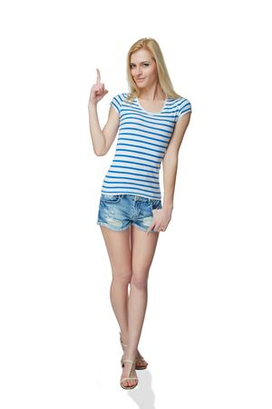 casually: Happy young denim girl in shorts standing casually in full length, pointing to the side at blank copy space, against white background