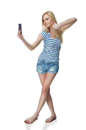 coquettish: Happy flirting young girl taking pictures of herself at smart phone, over white background