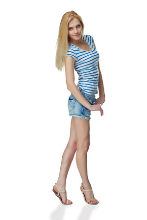 svelte: Full length of smiling young slim tanned female in denim, isolated on white background
