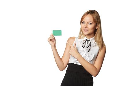 Muchacha sonriente feliz en ropa casual, mostrando la tarjeta de crédito en blanco, sobre fondo blanco Foto de archivo