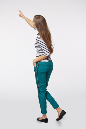 pointing at: Back view of full length business woman in pointing at copy space, on gray  Stock Photo