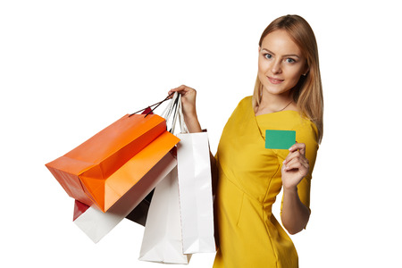 Shopping young woman in the yellow with bags and a credit card isolated on white background photo