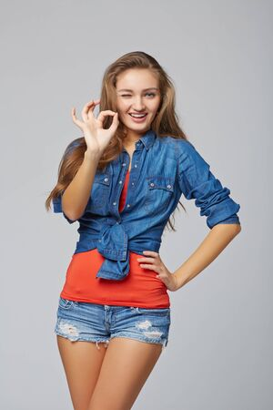 okay: Portrait of female okay gesturing, on gray background