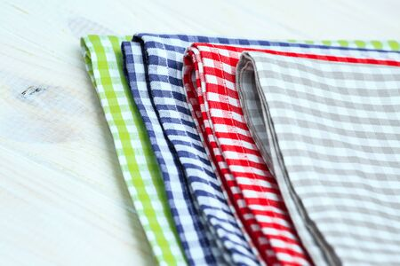 dishcloth: Multi-colored kitchen towels, on a white wooden background