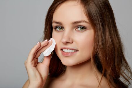removing make up: Pretty young woman removing make up, on gray background Stock Photo