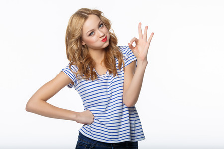 Young attractive female with thumbs-up and OK gesture on white background photo