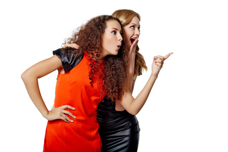 Two surprised girls friends with opened mouths pointing to blank copy space, isolated on white background