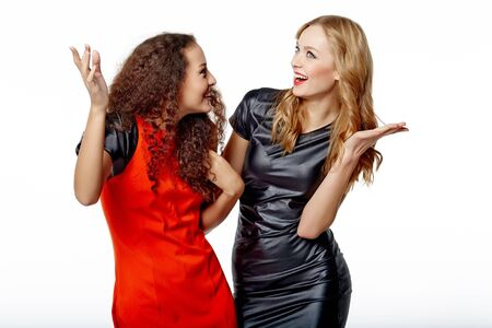agreeing: Happy females friends hugging and gesturing thumbs up, over gray background