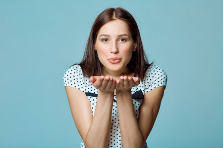 Lady beautiful woman blowing a kiss at you against blue background