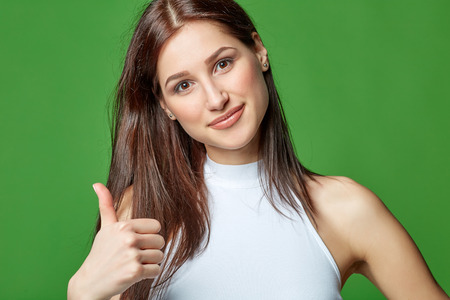 thumbup: Young cute smiling emotional girl giving you thumb up, on green background