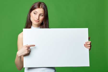 Beautiful woman gesticulating, holding white blank advertising board banner, on green background Imagens