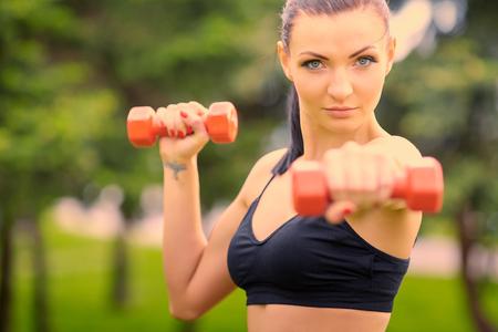 femme blonde: Femme instructeur de conditionnement physique exercice avec de petits poids dans le parc vert