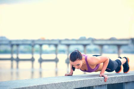 Sport, fitness, mensen en gewichtsverlies concept - mooie sportieve jonge vrouw over de stad aan het water achtergrond