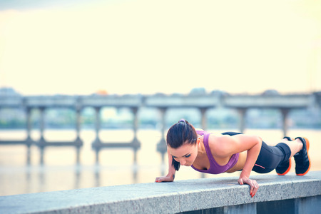 Sport, fitness, people and weight loss concept - beautiful sporty young woman over city waterside background