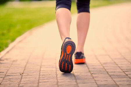 pathway: feet of an athlete running on a park pathway training for fitness and healthy lifestyle