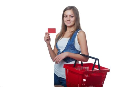 spending full: Shopping concept. Happy full length woman standing with empty red shopping basket and showing blank credit card, white background