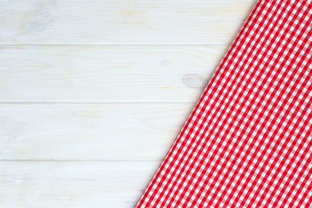 picnic cloth: Red towel over wooden kitchen table. View from above with copy space