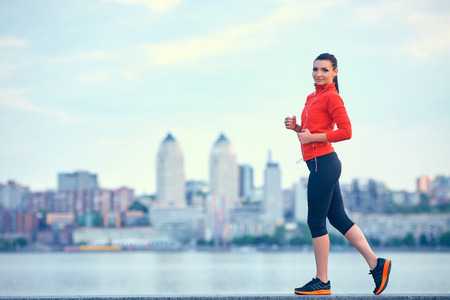 waterside: Sport, fitness, people and weight loss concept - beautiful sporty young woman over city waterside background