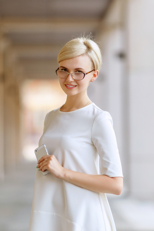 phone message: Portrait of a business woman smiling with cell phone outside office building.