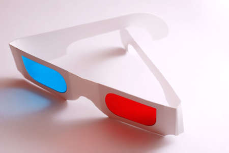 Stereo glasses with blue and red eyes laying on white table
