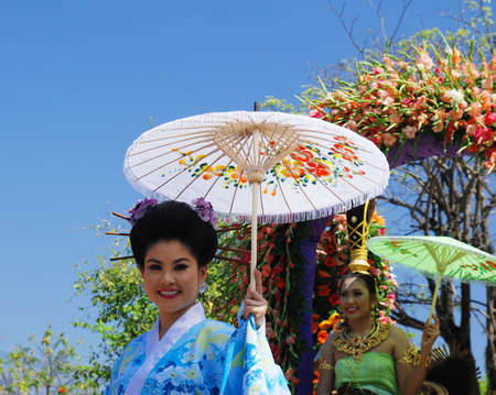 procession: CHIANG MAI - FEB 6: Traditionally dressed girl in procession on Chiang Mai 34th Flower Festival on February 6th, 2010. Chiang Mai, Thailand