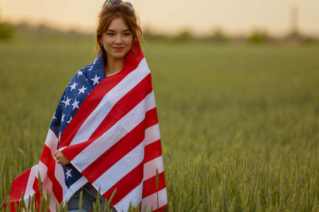 young happy beautiful caucasian teenager girl in pink top and jeans shorts with national american flag on her in green wheat field at sunset. Independence day