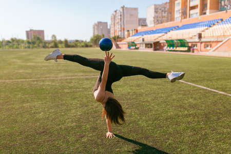 young good looking girl in black sport outfit doing gymnastics handstand in the splits in park with ball Banque d'images