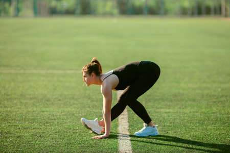 young good looking girl in black sport outfit doing stretching of here leg in park