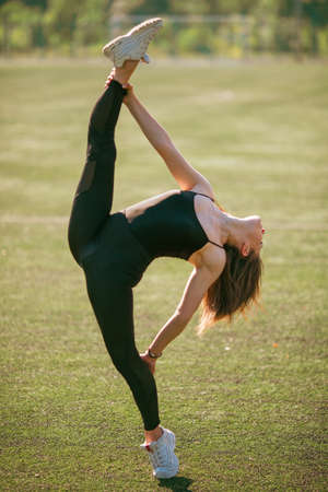 young good looking girl in black sport outfit doing gymnastics splits standing on one leg and holding other leg in park