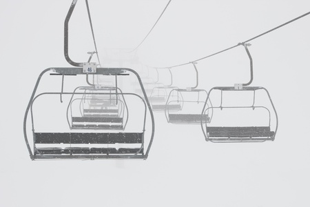 chairlift: ski chairlift in a foggy and snowy mountains Stock Photo