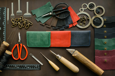 Leathersmiths work desk. Leather working tools on a work table