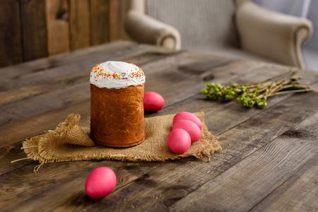 Easter cake and colorful eggs on a wooden table. It can be used as a background Фото со стока