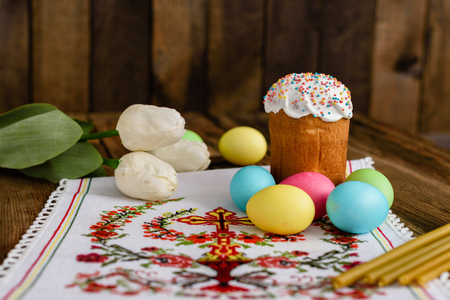 Easter cake and colorful eggs on a wooden table.