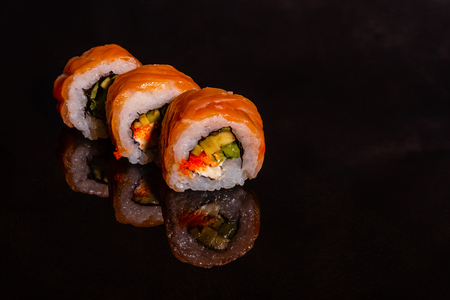 Fresh and tasty sushi on dark background. It can be used as a background 免版税图像