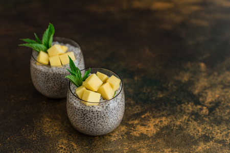 Beautiful and tasty dessert with mango and seeds of a chia. A fresh pudding for breakfast 免版税图像