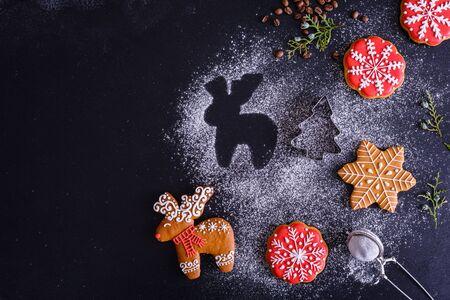Biscotti di pan di zenzero fatti in casa di Natale su uno sfondo scuro Archivio Fotografico