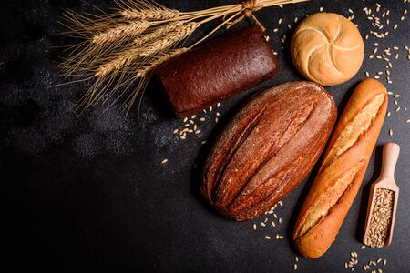 Fresh fragrant bread with grains and cones of wheat against a dark background. Assortment of baked bread on wooden table background. Fresh fragrant bread on the table. Food concept.