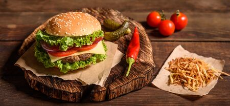 Tasty grilled homemade burger with beef, tomato, cheese, cucumber and lettuce. Delicious grilled burgers. Craft beef burger and french fries on wooden table. Banco de Imagens