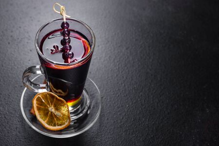 Christmas hot mulled wine with cinnamon cardamom and anise on a dark background. Glass mugs of hot mulled wine with spices and citrus fruits