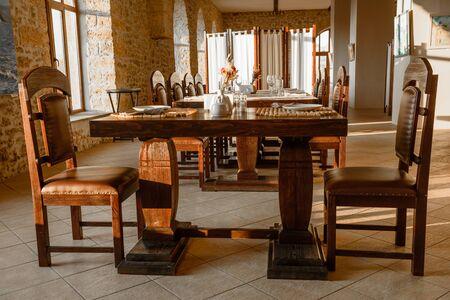 Glasses, flower fork, knife served for dinner in restaurant with cozy interior. Empty glasses in restaurant