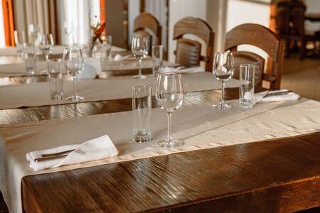 Bicchieri, forchetta per fiori, coltello serviti per cena in un ristorante con interni accoglienti. Bicchieri vuoti al ristorante