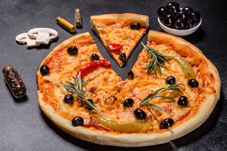 Tasty fresh hot pizza against a dark background. Pizza, food, vegetable, mushrooms. It can be used as a background