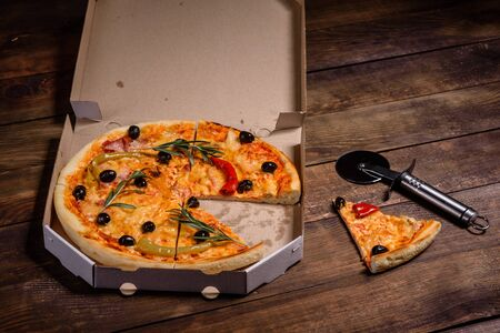 Tasty fresh hot pizza against a dark background. Pizza, food, vegetable, mushrooms.  It can be used as a background Stock fotó