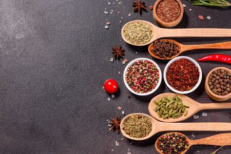 A set of spices and herbs. Indian cuisine. Pepper, salt, paprika, basil and other on a dark background. Top view. Free copy space. 版權商用圖片